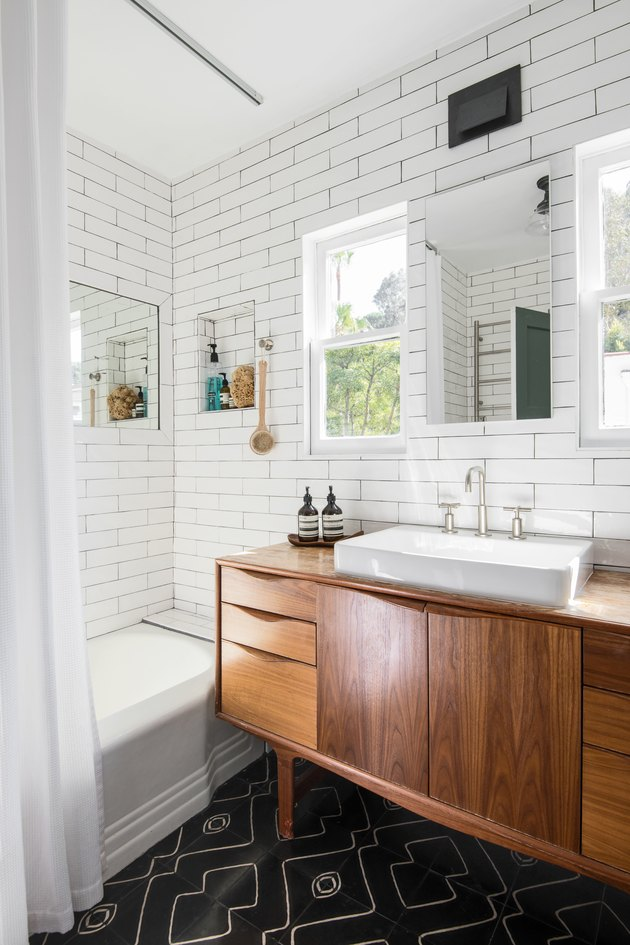 wood vanity with white vessel sink, rectangular mirror, white subway tile wall, white bathtub, white shower curtain, black tile floor with design