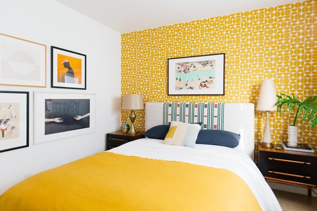 bedroom with yellow wallpaper and bedding and framed prints on the wall
