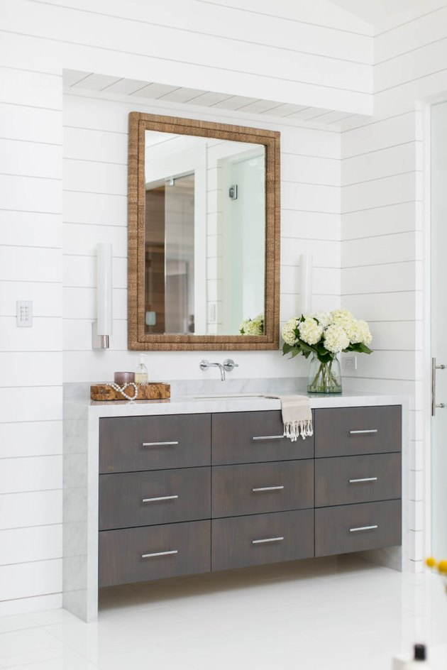 bathroom space with shiplap walls and dark cabinets