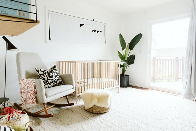 White baby nursery idea with light wood crib and rocking chair