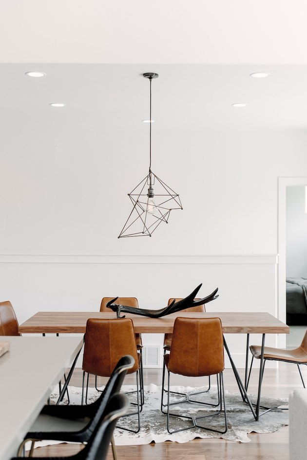 minimalist dining room with leather dining chairs and abstract pendant