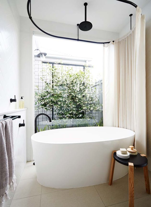 modern bathtub shower combination with oval tub and large window