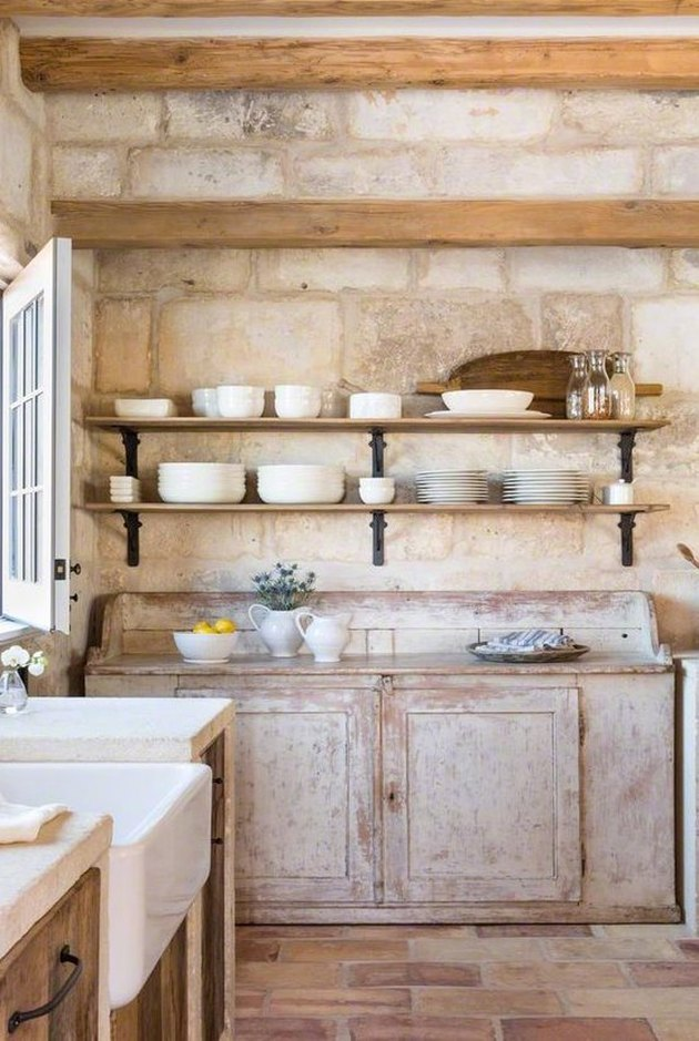 rustic farmhouse kitchen with distressed cabinets and brick floor