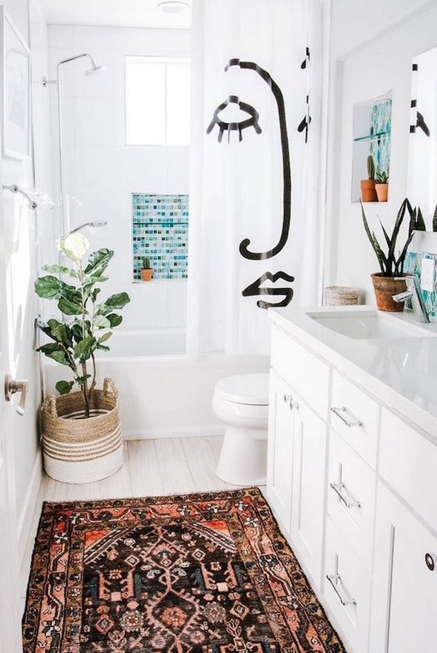 white bathroom with potted plant and area rug