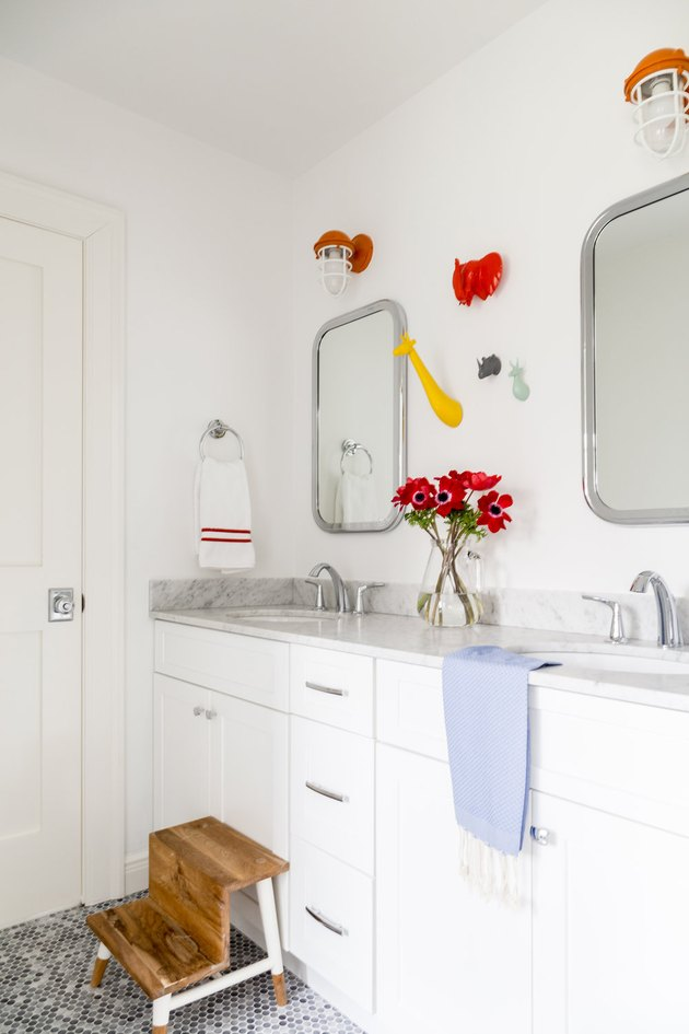 bathroom space with white cabinets and two mirrors