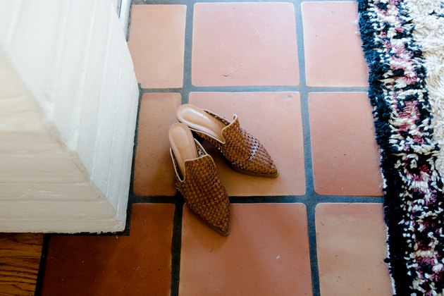 Saltillo tile detail with shoes and area rug