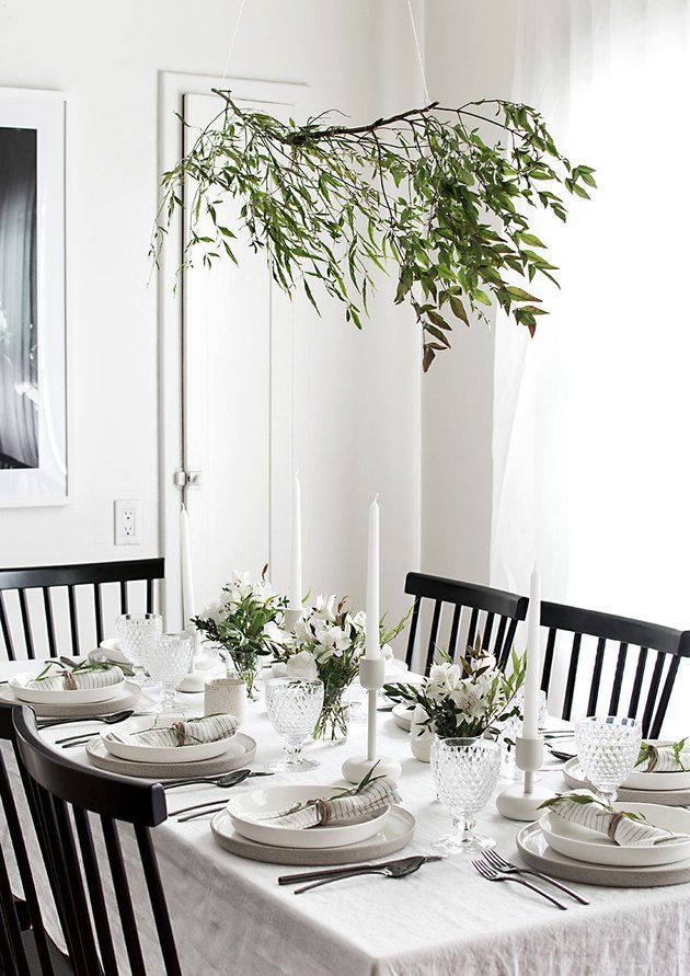 modern white dining room with black chairs and greenery