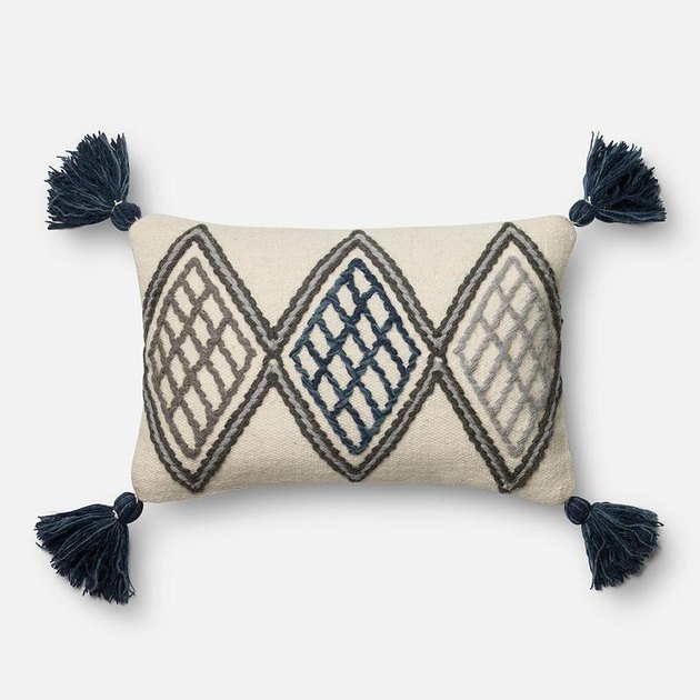 black and white patterned pillow with tassels
