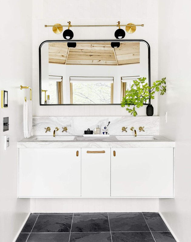 bathroom space with black floor, white cabinets, and one large mirror