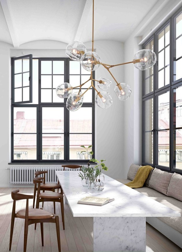 modern dining room with statement chandelier and black window frames