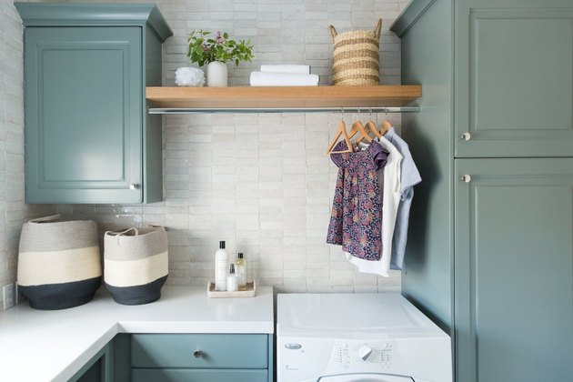 blue-green laundry room idea with cabinets and storage baskets