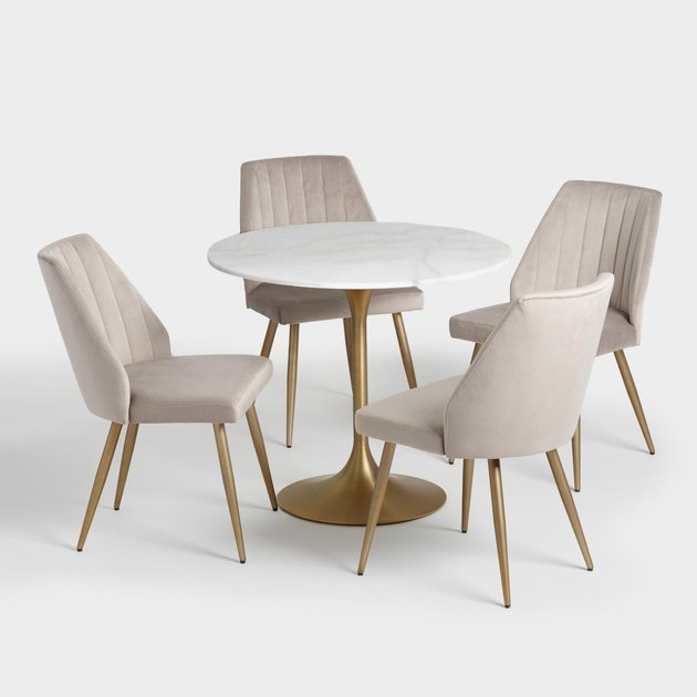 marble and gold round dining table with tan chairs
