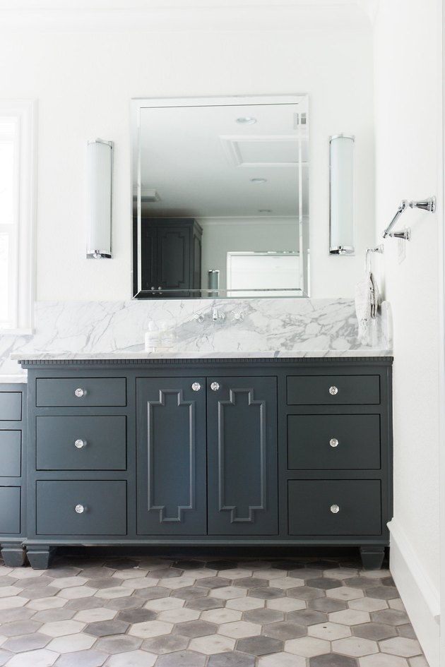 bathroom space with gray and white tiles and dark cabinets