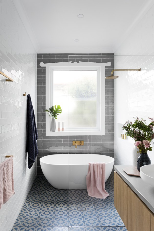 walk-in bathtub shower combination with gray accent wall and patterned tile floor