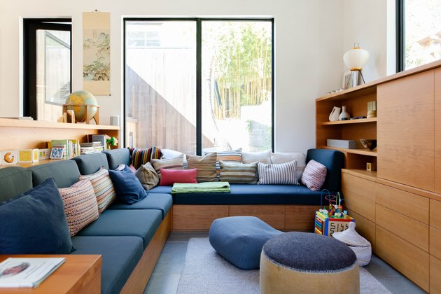 Modern blue kids' playroom idea with wood furniture and throw pillows