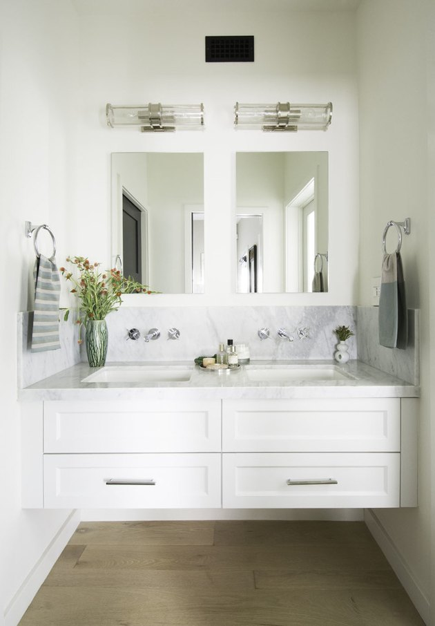 bathroom space with two mirrors, white cabinets, and hardwood floor