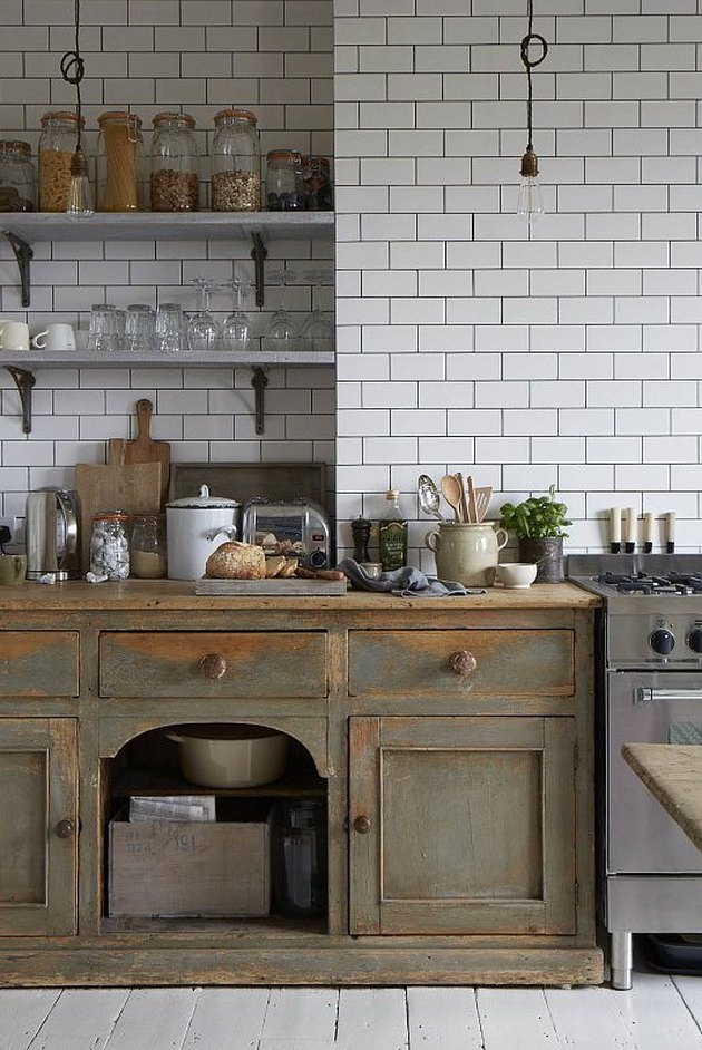 modern kitchen with green distressed cabinets and white subway tile backsplash