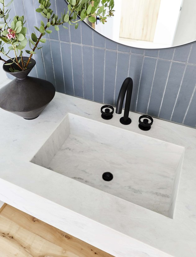 marble sink with blue tiles in the background