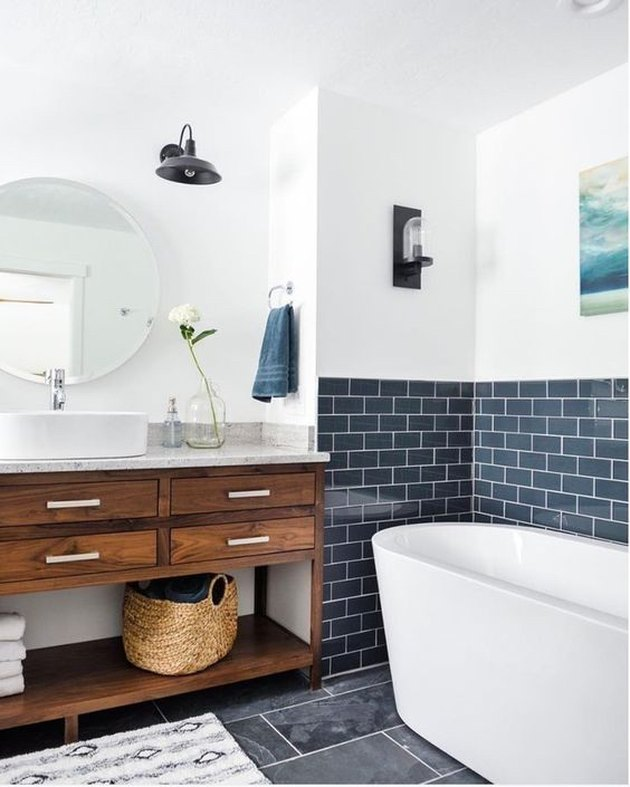bathroom tub backsplash idea with bluish-gray subway tile behind freestanding tub