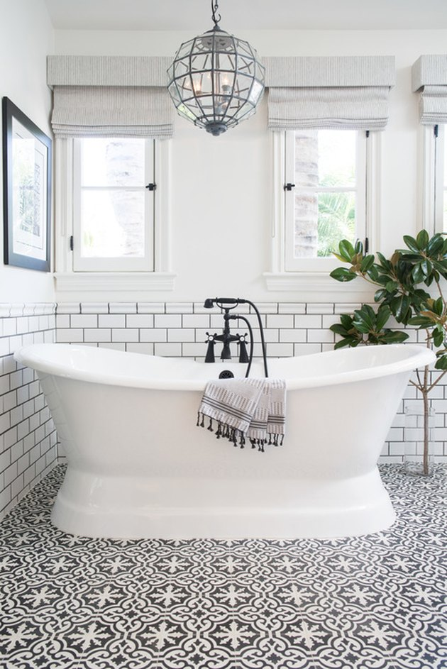 bathroom tub backsplash idea with white subway tile and black grout behind freestanding tub