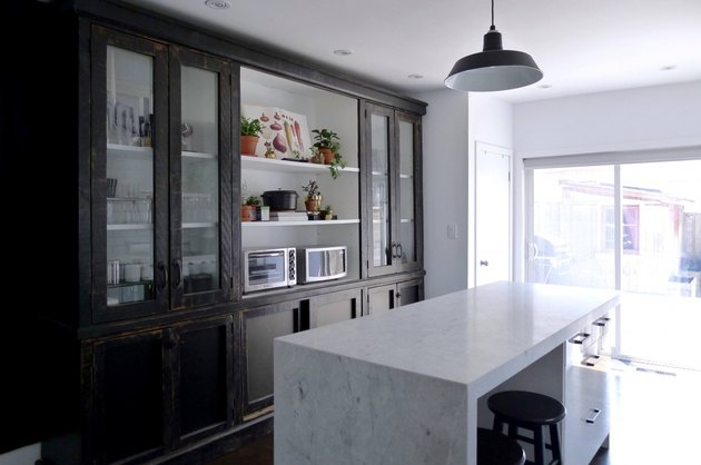 modern kitchen with black distressed cabinets and industrial pendant light