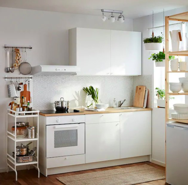 kitchen space with white cabinets and white storage cart