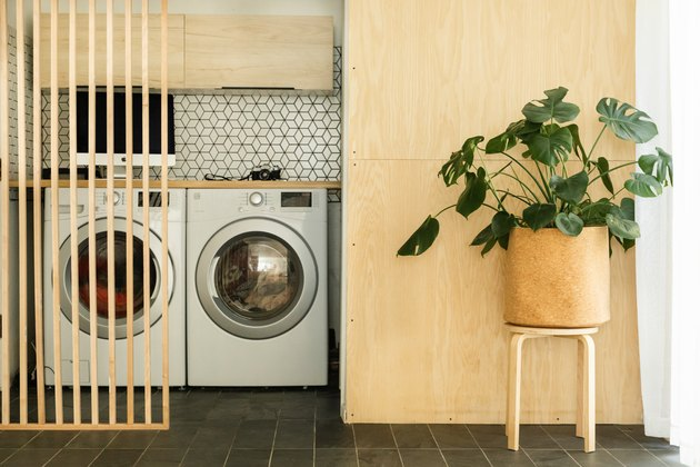 laundry room idea with light wood and patterned backsplash behind appliances