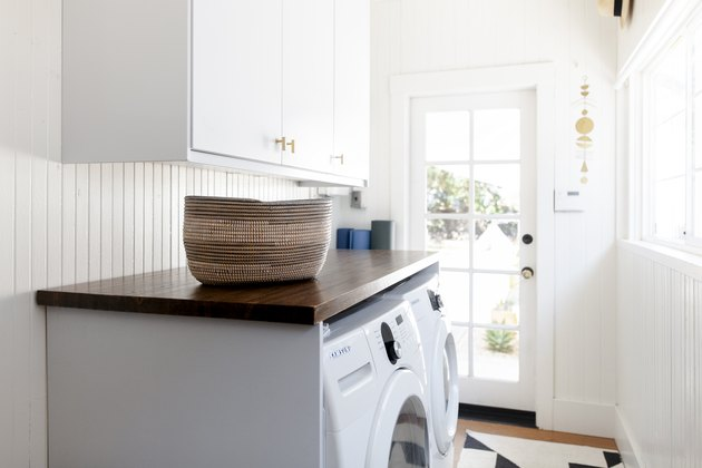 white laundry room with wood countertop and closed cabinets