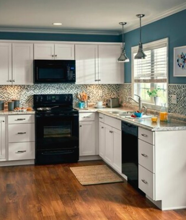 kitchen space with white cabinets and blue walls