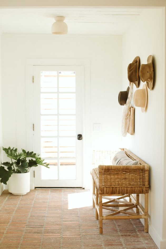 entryway idea with hats displayed on wall above accent bench with terra cotta flooring
