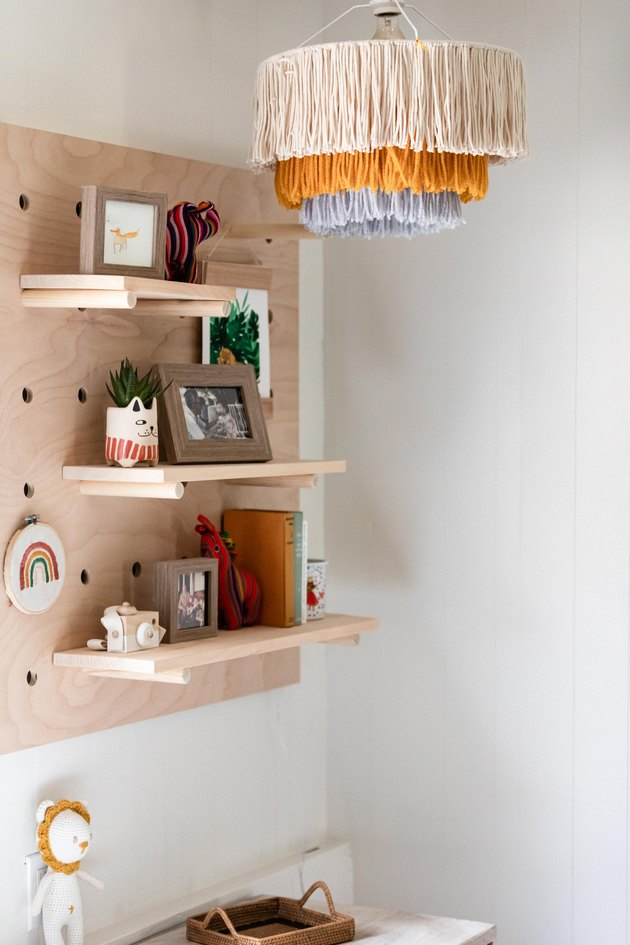 playroom idea with fringe chandelier and pegboard shelving