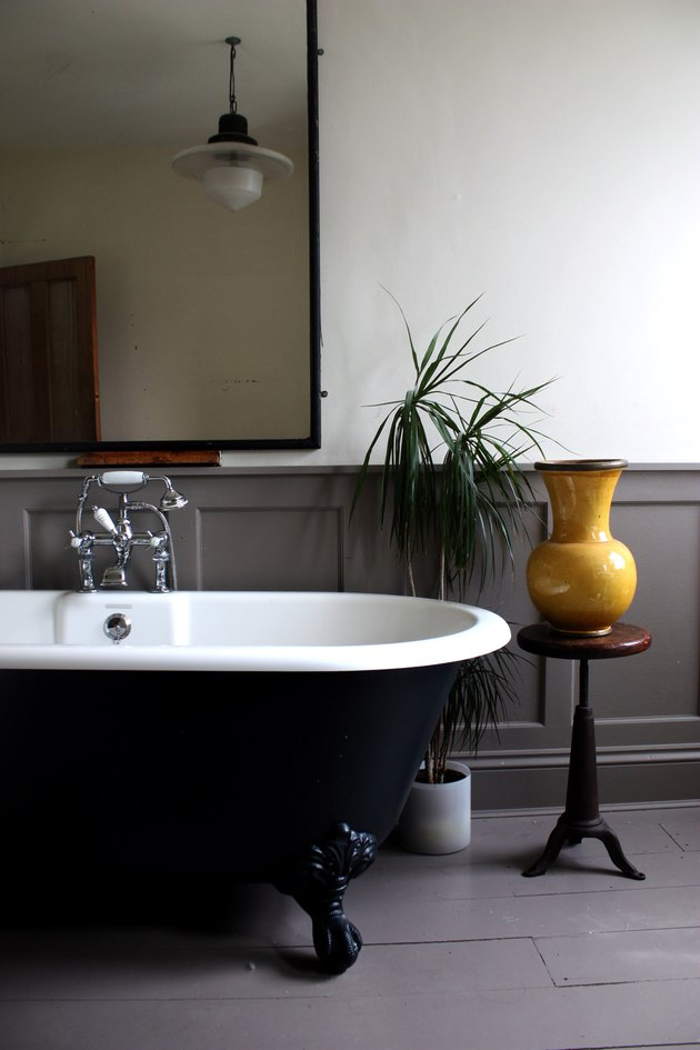 dark bathtub with gray panelled walls