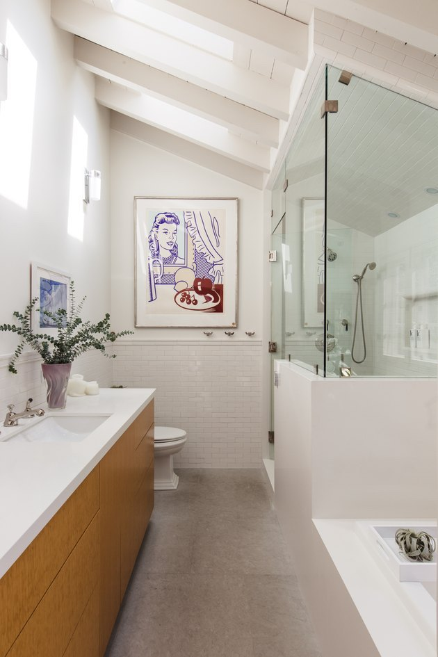 white bathroom with angled ceiling and retro artwork