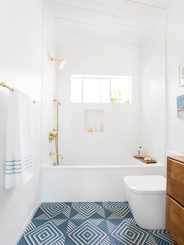 white bathroom with brass fixtures and blue patterned flooring