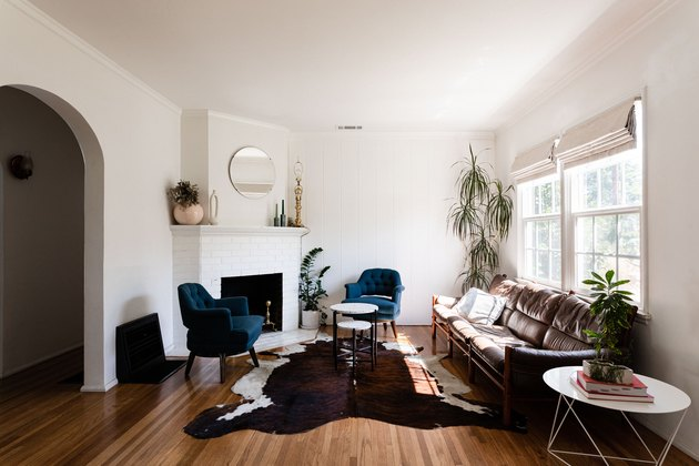 living room idea with leather sofa and cowhide rug in front of fireplace