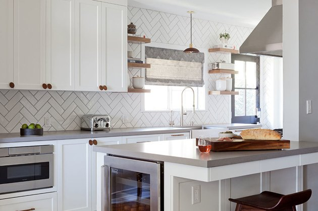 white kitchen with shaker cabinets and herringbone subway tile
