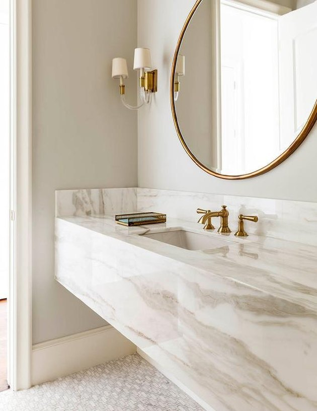 bathroom with marble backsplash and gold hardware