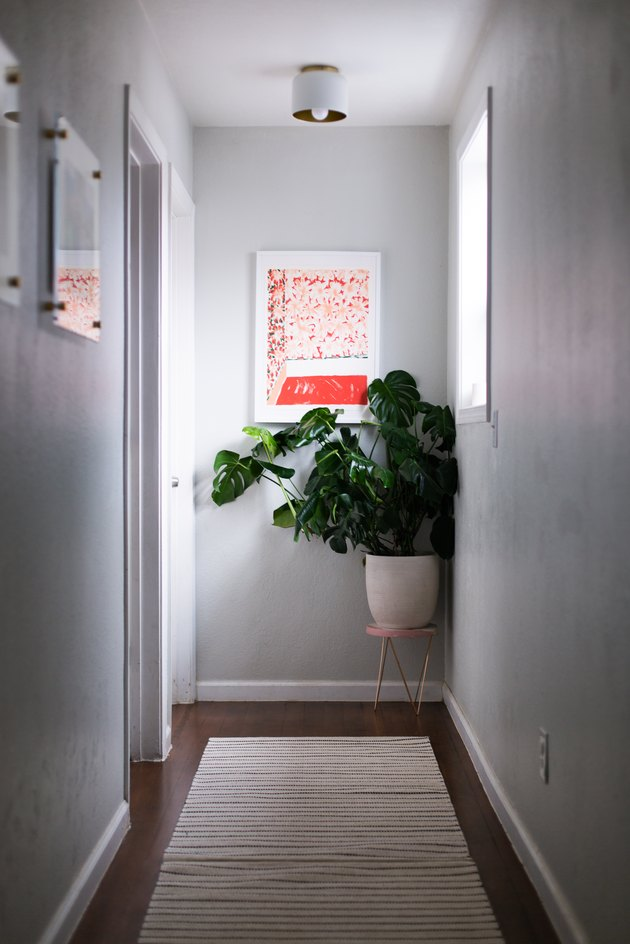 hallway idea with small side table for potted plant and artwork hung on wall