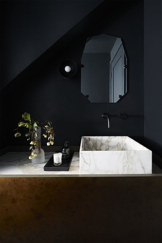 black bathroom with marble vessel sink and black fixtures