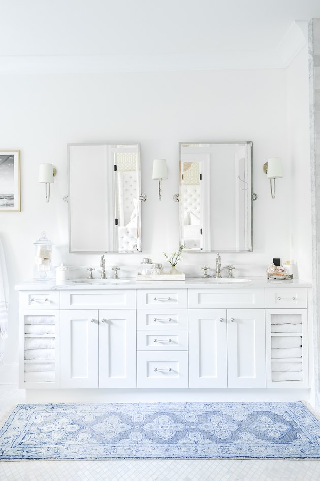 bathroom with white cabinets, marble backsplash, two mirrors, and blue rug