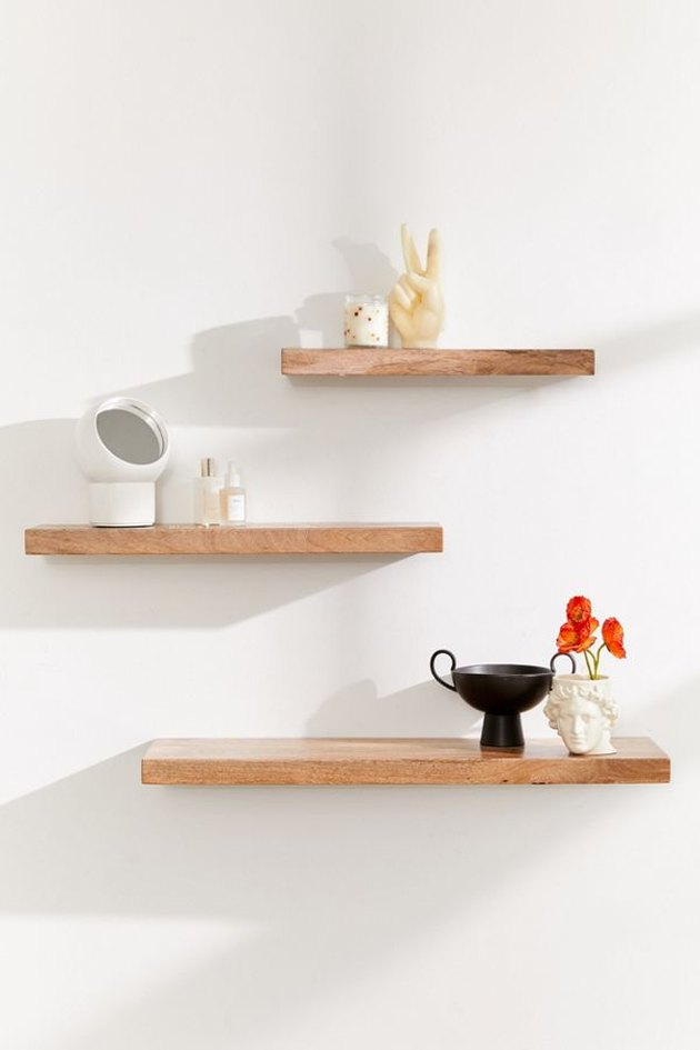 Three wooden floating shelves in various sizes in medium finish