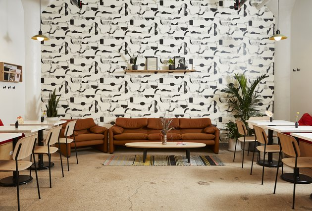 seating area with graphic black and white wallpaper, brown couch, light wood chairs and tables