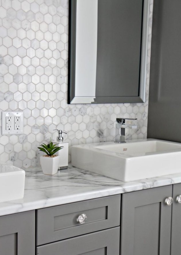 bathroom with gray cabinets and marble laminate countertop