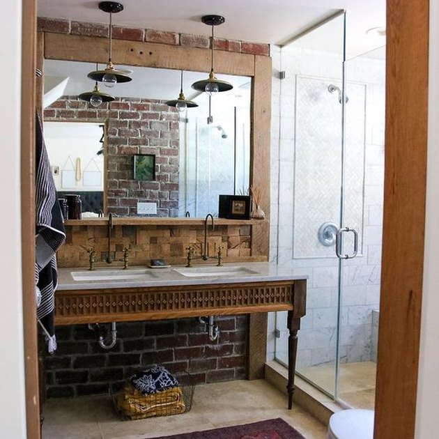 modern farmhouse bathroom with brick walls and rustic vanity with Carrera marble countertop