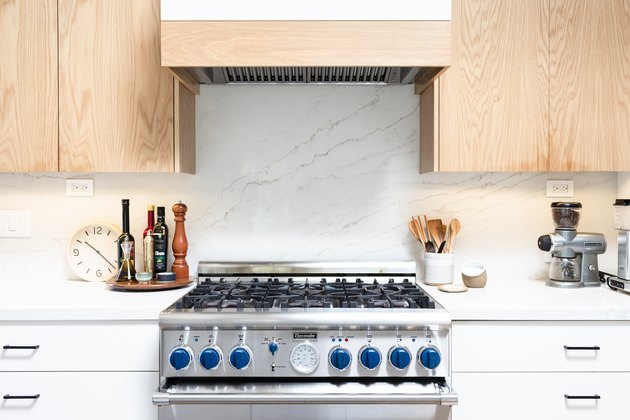 close-up of gas range, cabinets, vent hood