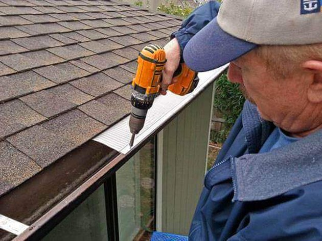 Contractor attaching gutter guard to gutter.