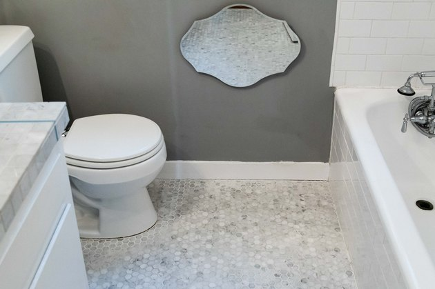 mosaic tile bathroom floor, mirror on wall reflecting tile