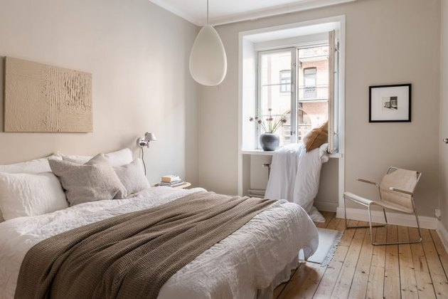 Scandinavian inspired beige bedroom with wood flooring and white trim