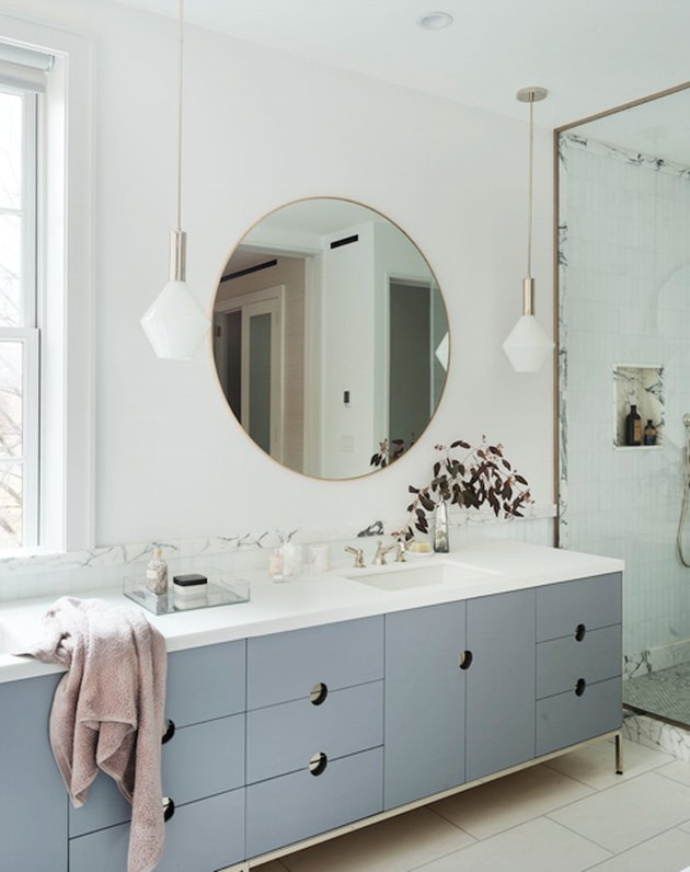 minimalist bathroom with blue cabinets and large round mirror