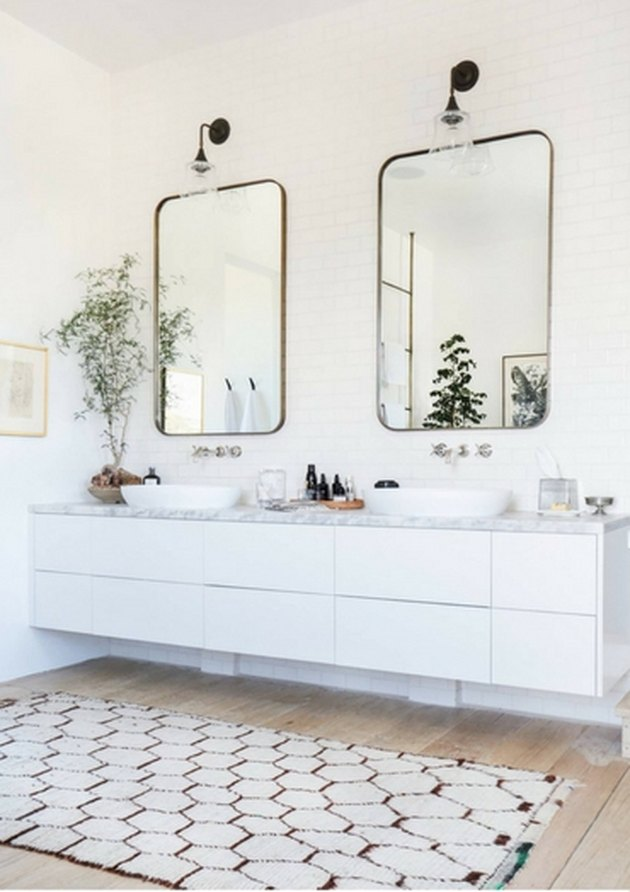 his and hers sinks in master bathroom with wood flooring